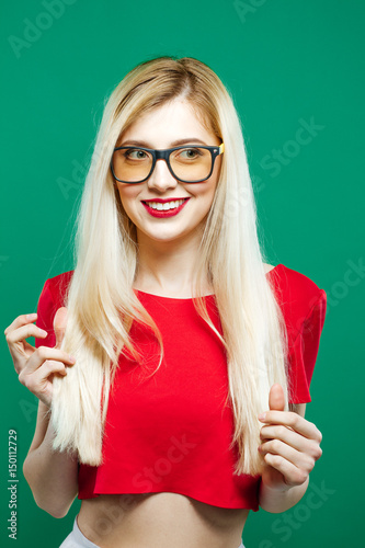3c27256ae4e Young Girl Wearing Short Red Top and Eyeglasses is Posing on Green  Background. Portrait of Sensual Pretty Blonde in Studio.