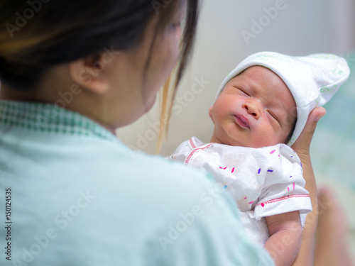 Plakat Macierzysty mienie jej nowonarodzony dziecka dziecko po pracy w szpitalu.