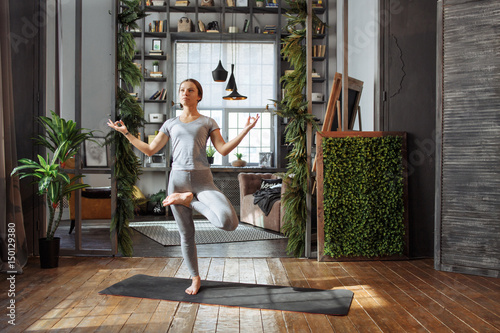 Fototapeta Young woman in homeware practicing balance yoga pose on carpet in her comfy bedroom. obraz na płótnie