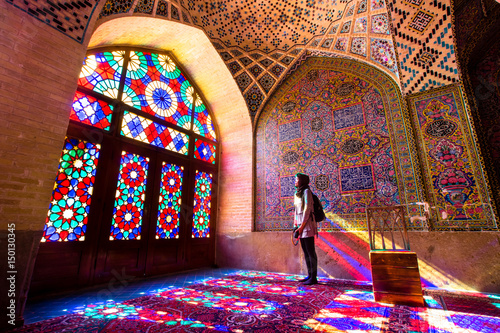 Obraz na plátně  An asian female tourist facing the multicolors light through spectacular stained glass in Nasir Al-Mulk Mosque (Pink Mosque) in Shiraz - Iran