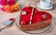 Herzförmiger, roter Kuchen mit Rosen auf Holztisch