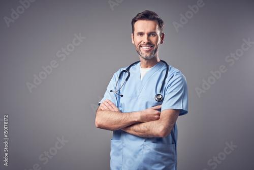 Fotografía  Happy doctor in blue uniform smiling isolated
