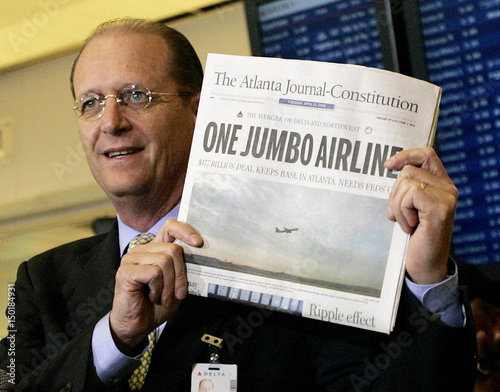 Delta CEO Richard Anderson holds up a local paper showing