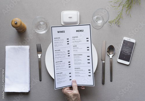 restaurant patron with menu and smartphone mockup 2 buy this stock