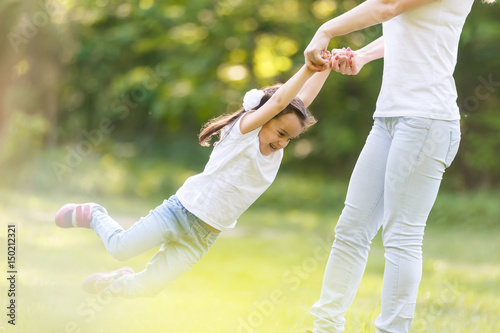 Photo  Mother and daughter playing circling around at the park on beautiful morning