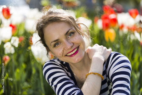 Smiling woman in front of spring flowers Poster