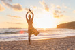 Silhouette of young woman practicing standing tree yoga pose on sandy beach at sunset.