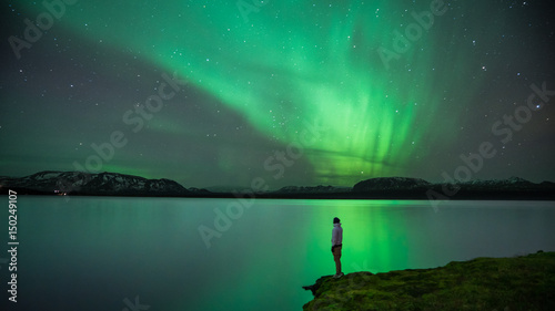 Canvas Prints Northern lights Man with Northern Lights reflection