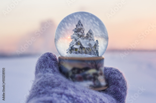Foto op Plexiglas Kerstmis Girl in knitted mittens holding glass ball with firtrees, house and artificial snow falling inside the ball with winter landscape at the background