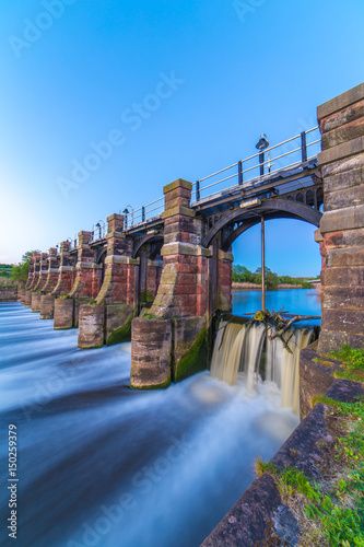 Obraz na plátne River weaver sluice gates Northwich Cheshire UK at sunset