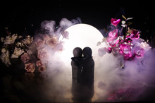 Two Doll Hugging On Table With Flowers And Moon Decoration Lighted Background With Smoke.Love Concept. Greeting Or Gift Card Design Idea. Vintage Tone. Silhouette Of Hugging Couple