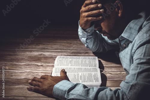 Fotografia  Worried man reading the Holy Bible