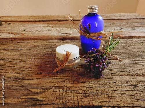 Fotografia Pequenos vidros de hidrantante enfeitados com ráfia e buque de mini flores do ca