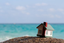 A Toy House On A Background Of Sea Waves. Sandy Beach.