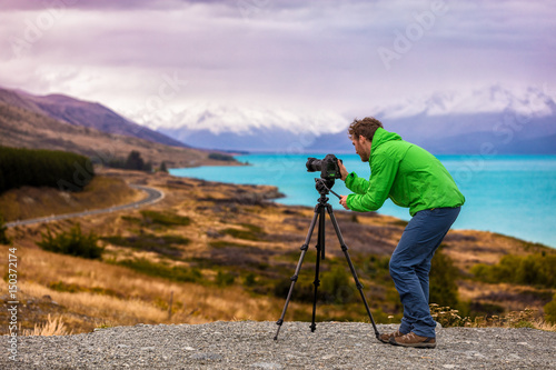 Tuinposter Purper Travel photographer taking nature landscape pictures in New Zealand at sunset. Man shooting at Peter's lookout, famous tourist attraction at Pukaki Lake.