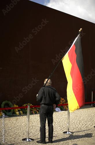 Former East German holds a German flag near the Berlin Wall