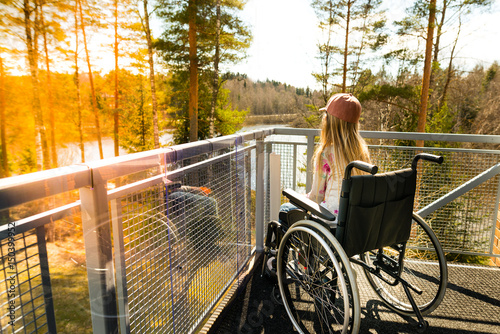 Foto  Young girl in a wheelchair on a balcony looking at the nature in the spring