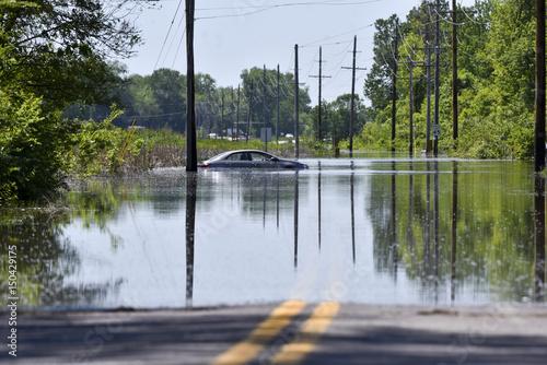 Plakat Samochód osierocony na zalanej drodze