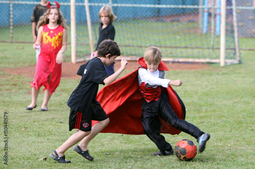 school children wearing halloween costumes play soccer during a halloween carnival at the american