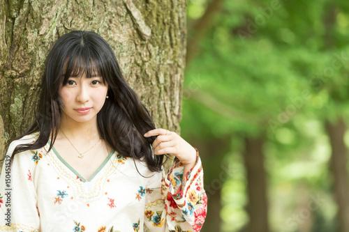 若い女性 ポートレート 公園 黒髪を触る カメラ目線