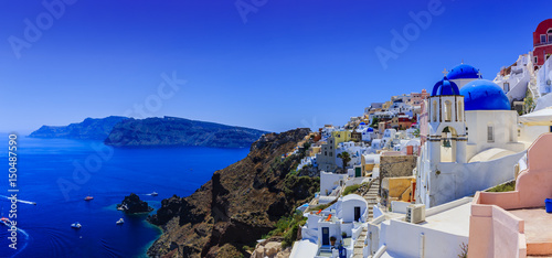 Fototapeta Picturesque view of Old Town Oia on the island Santorini, white houses, windmills and church with blue domes, Greece obraz