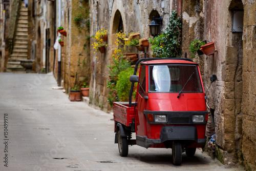 In de dag Aap Piaggio Ape at the empty street