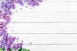 canvas print picture Floral pattern made of blue lilac branches and petals on white wooden background. Flat lay, top view. Floral purple frame