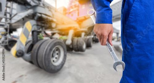 Plakat Mechanik z ramionami krzyża z dużym kołem dźwigu w porcie jest w tle.