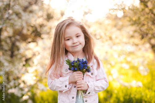 Smiling baby girl 4-5 year old holding flowers outdoors ...  Smiling baby gi...