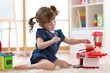 Little cute girl playing with utensil toys. Toddler kid in a playroom. Kid sitting on floor and cook in toy kitchen.