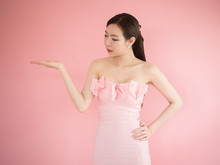 Sexy Woman Looking Something On Hand, Asian Girl Wear Strapless Dress And Posing On Pink Background, Sweet Fashion Concept.