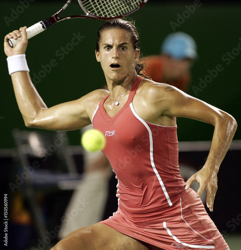 Amelie Mauresmo of France hits a return against Kim ...