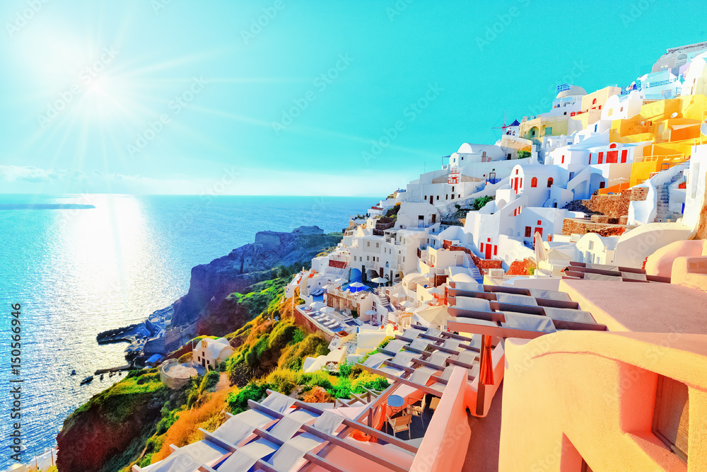 Fototapety, obrazy: Breathtaking scenery of Oia village traditional Greek island architecture at Aegean sea and noon zenith sun flare background. Santorini island, Greece, Europe. Santorini is famous and popular resort.