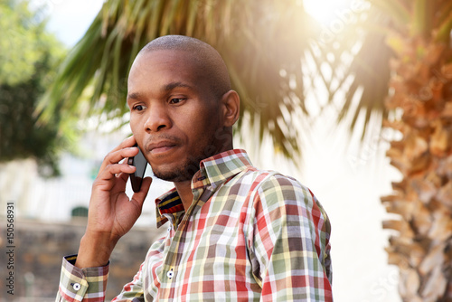 handsome young african man talking on mobile phone outside Canvas Print