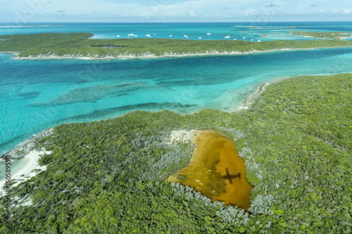 Staande foto Tropical strand Aerial photo looking down at the airplane's shadow and clear tropical water and islands in the Exuma Chain of islands the Bahamas near Staniel Cay.