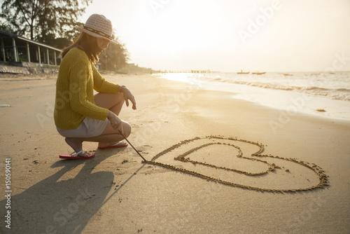 Photo  Beautiful woman writing message (heart symbol) on sand beach.