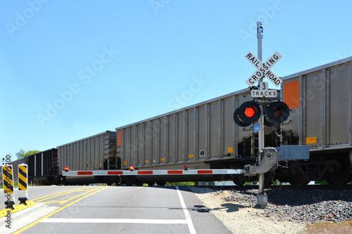Valokuvatapetti Freight train at crossing gate