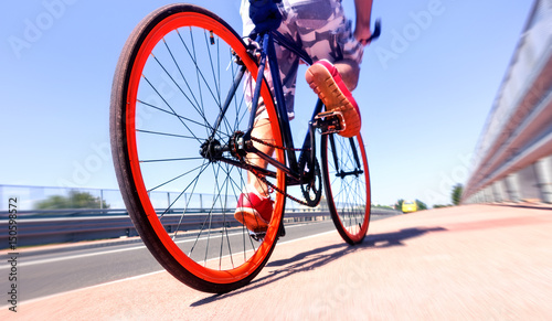 Man cycling on sport bike - Bicycle wheels and road perspective with cyclist rid Fototapeta