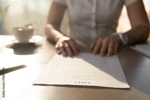 Photo Woman sitting at the desk with loan agreement form