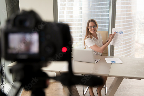 Attractive Woman Sitting At Desk With Laptop And Showing Doent Stats On Camera Female