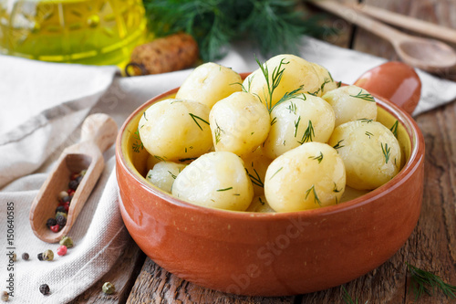 Boiled potatoes with dill on a wooden background