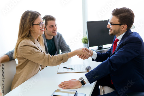 Tableau sur Toile Young couple in bank office shaking hand to financial adviser.