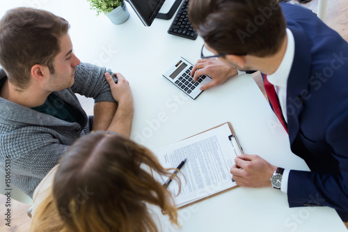 Business man explaining terms of contract to his clients in the office.