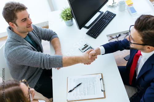 Canvas Print Young couple in bank office shaking hand to financial adviser.
