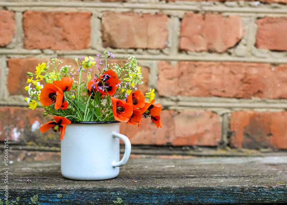 Beautiful bouquet of bright wildflowers in mug. Rustic. Selective focus.