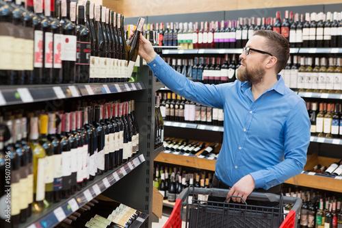 Fototapeta Mature bearded man shopping at the wine supermarket