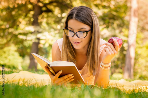 Fotografie, Obraz  outside portrait of young beautiful woman with apple reading book in park
