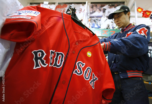 A Japanese fan of Boston Red Sox look through uniforms at
