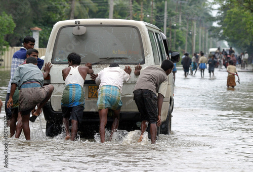 Sri Lankan Tamil villagers push a van through floodwaters at highway