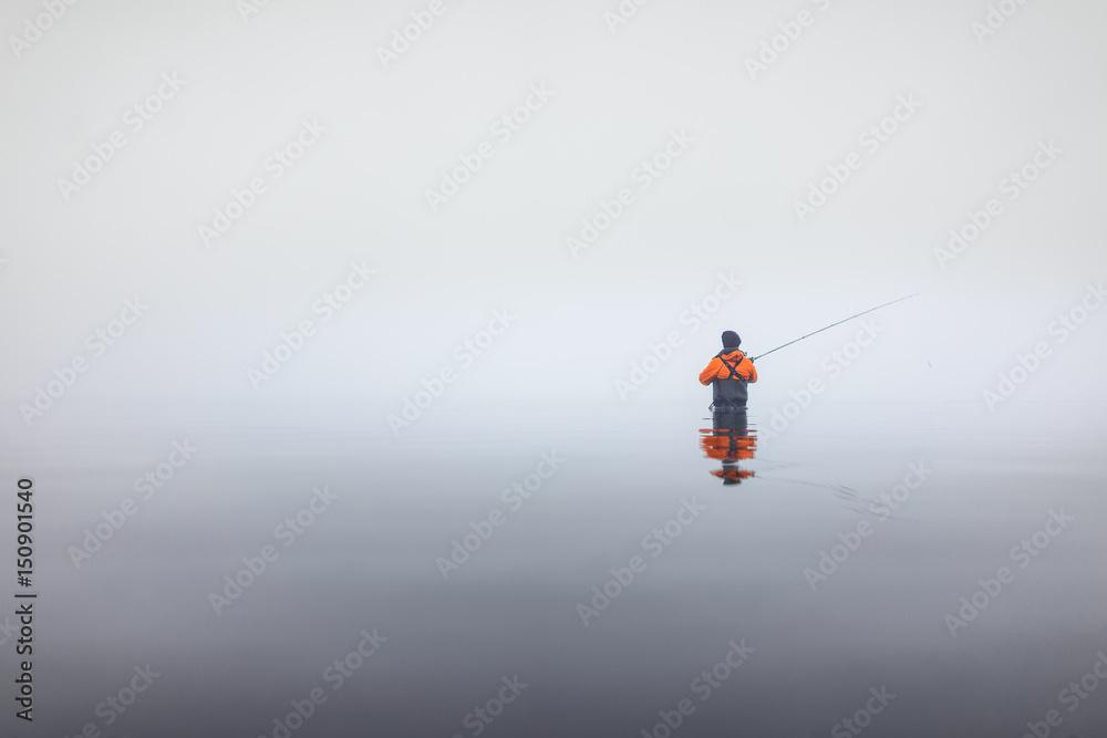 Angler in Wathose mit Angelrute im Wasser bei Nebel an der Küste im ...